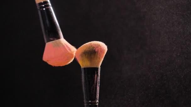 Kozmetikai koncepció. Kozmetikai kefe pasztell rózsaszín kozmetikai por, fekete háttér