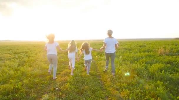 Koncept přátelství. Mladé ženy šťastný se svými dcerami běží přes pole při západu slunce
