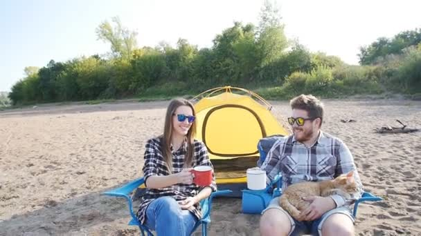 Concept of tourism and travel. Young happy couple sitting in tent watching the view