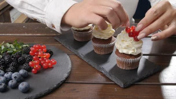 Koncept malých firem a cukrovinek. Ženské baker zdobení chutné košíčky s ovocem