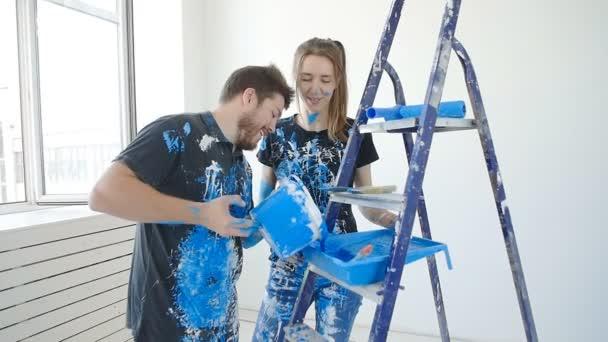 Šťastný pár okouzlující baví a malování pokoje v jejich novém domě