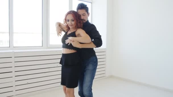 Young couple dancing social dancing kizomba or bachata or semba in dancing class indoors