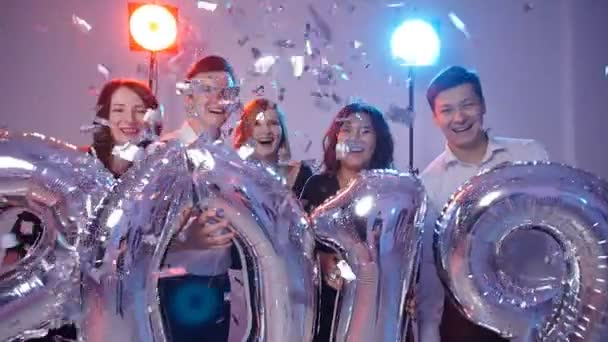 Konzept für das neue Jahr 2019. Gruppe fröhlicher junger Leute mit Luftballons, überschüttet mit Konfetti
