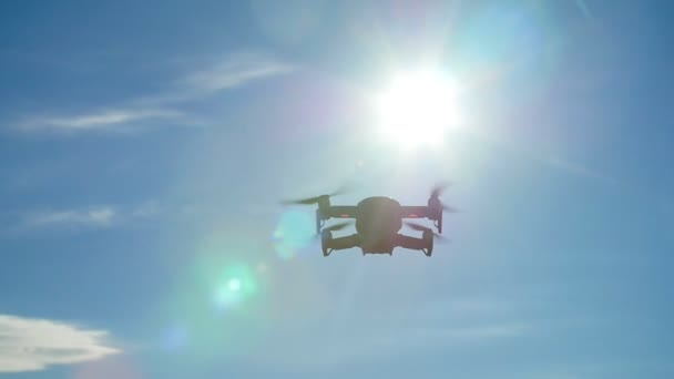 The concept of personal drones and aerial photography. Quadcopter flying overhead in cloudy blue sky