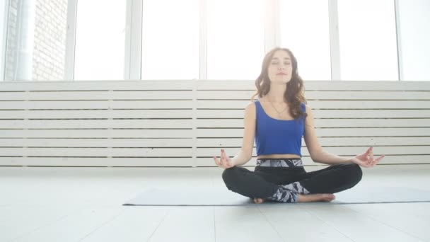 Sporty young woman practicing yoga, sitting in Half Lotus exercise, Siddhasana pose, indoor, home interior background