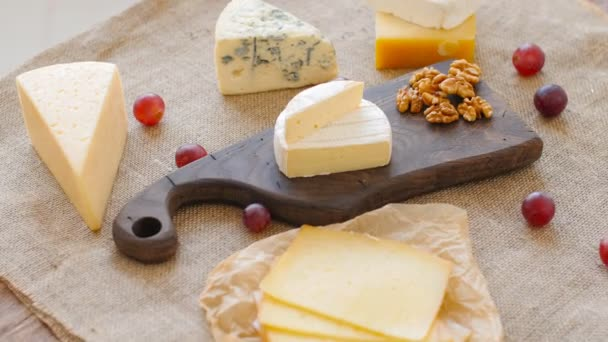 Cheese platter with nuts and grapes on a wooden cutting board