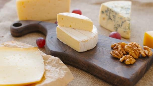 Sýrový talíř s ořechy a hrozny na dřevěném prkénku