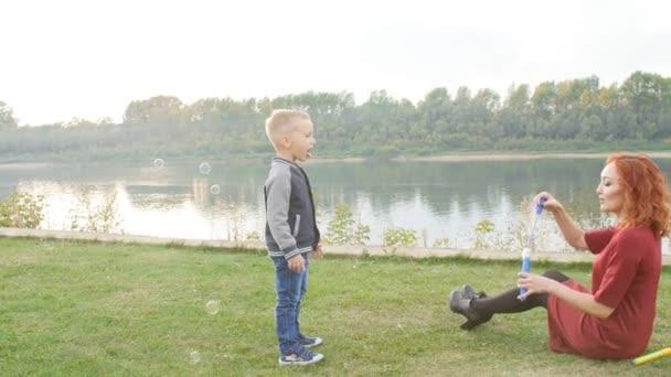 Rodina a děti koncept. Mladý pár se dvěma syny walking řekou