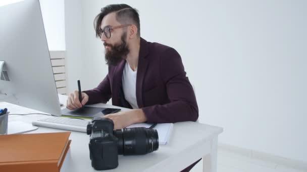 Konzept der professionellen Fotografie und Grafik-Design. Stilvolle Jüngling Grafik Designer, Fotografen, die an ein Grafiktablett im Büro arbeiten
