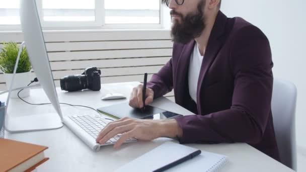 Elegantní mladý muž grafické návrháře, fotograf pracuje na grafickém tabletu v kanceláři