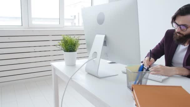 Pojem úřad práce nebo volné noze. Mladý vousatý stylový muži, kteří pracují u počítače v kanceláři
