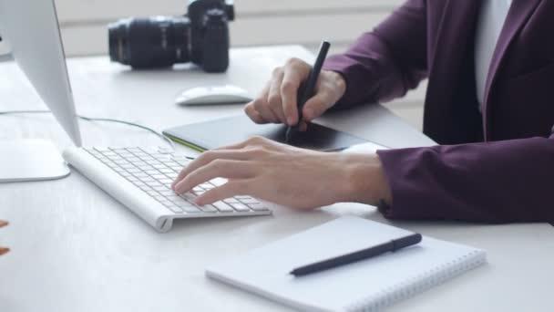Koncept profesionální fotografie a grafického designu. Mladý samec grafické návrháře, fotograf pracující v kanceláři nebo doma