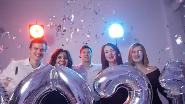 New year 2021 concept. Group of cheerful young people holding number balloons, showered with confetti