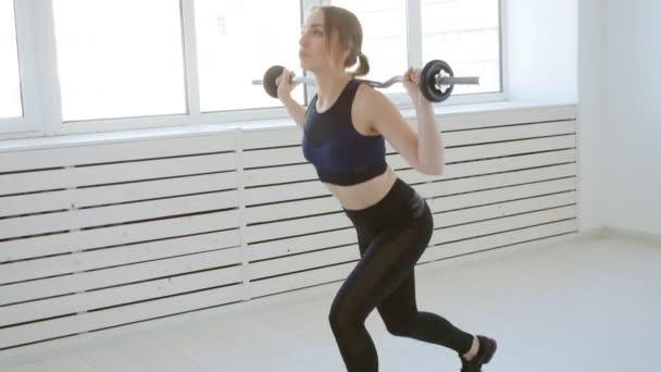 Domácí fitness koncept. Mladá žena s činka dělá cvičení v bílý interiér