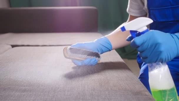 Koncepce čištění bytu nebo kanceláře. Pracovník čistí pohovky s kartáčem