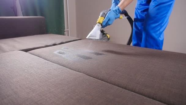 Koncepce čištění v byt a kancelář. Pracovník čistírny odstraňování nečistot z pohodlí pohovky uvnitř