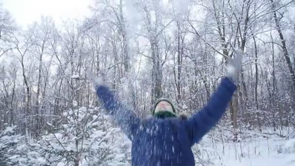 A tinédzser fiú havazik a téli erdőben. Aktív életmód, téli tevékenység, szabadtéri téli játékok koncepciója