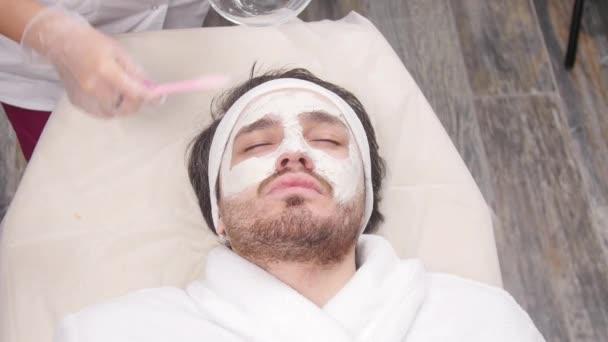 Kozmetikai és spa szolgáltatások fogalmának. Fiatal férfi agyag arcpakolás a beauty spa