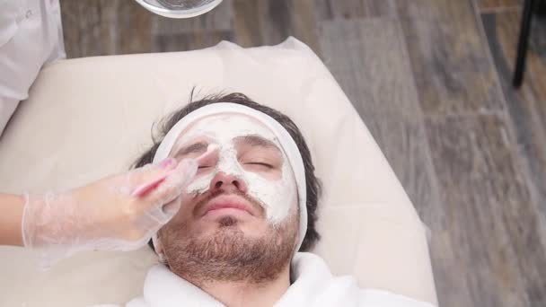 Concept of Cosmetic and spa services. Young Man with clay facial mask in beauty spa