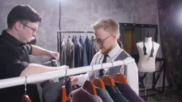 Koncept nákupu. Prodávající pomáhá mladý muž si vybrat oblek v úložišti