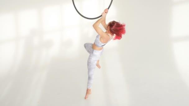 Nő az acrobat a hula hoop-a fehér háttérben