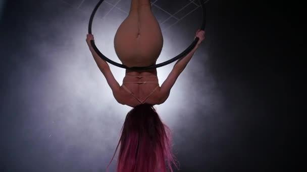 Konzept von Tanz und Akrobatik. junge schöne Frau in Antennenreifen mit farbiger Hintergrundbeleuchtung