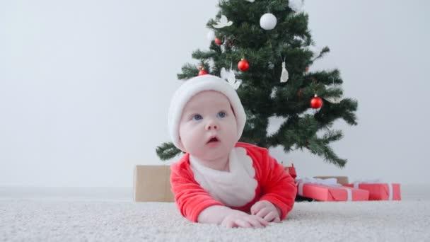 niedliches Baby im Kostüm von Weihnachtsmann, suchen ein Geschenk