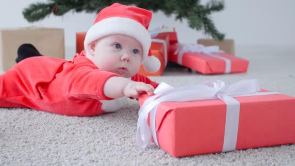 Weihnachtskonzept. niedliches Baby im Kostüm von Weihnachtsmann, suchen ein Geschenk