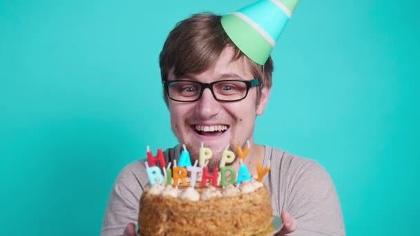 Konzept von Feiern und Spaß. lächelnd glücklich verrückter junger Mann mit Partyhut und Geburtstagstorte
