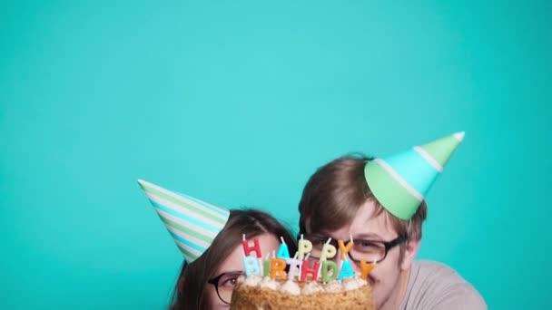 Koncept svátků a narozenin. Mladý veselý, zábavný pár s narozeninovým koláčem