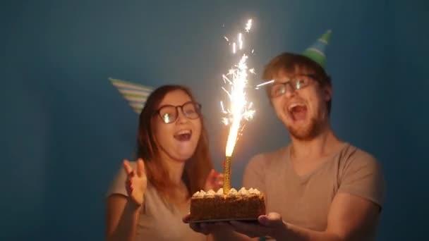 Konzept von Urlaub und Geburtstag. junges fröhliches lustiges Paar hat Spaß mit Geburtstagstorte