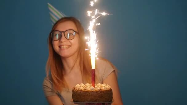 Koncepció az ünneplés és a szórakozás. Fiatal vidám vicces lány születésnapi tortával