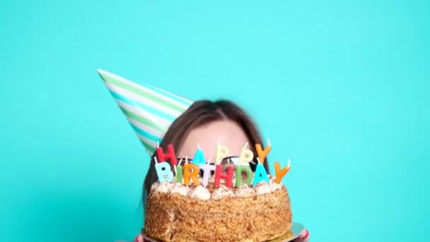 Koncept oslavy a zábavy. Mladá veselá dívka s narozeninovým koláčem