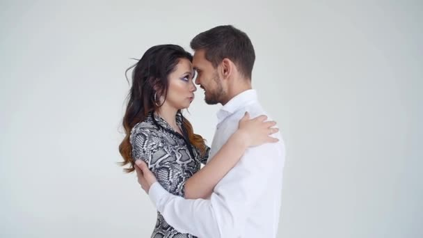 Concept of love, relationships and social dancing. Young beautiful couple dancing sensual dance on a white background