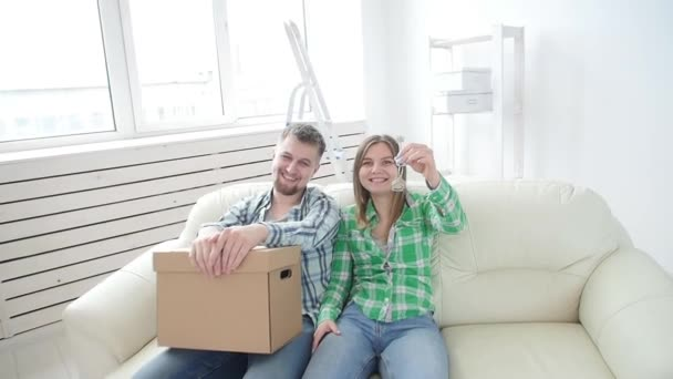 Concept of buying and renting real estate. Happy young couple showing keys of new home