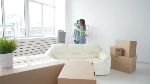 Concept of buying and renting real estate. Lucky couple embracing in new house