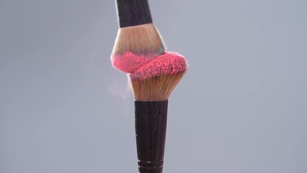 Make-up Pinsel mit rosa Puderspritzern Explosion auf grauem Hintergrund in Zeitlupe