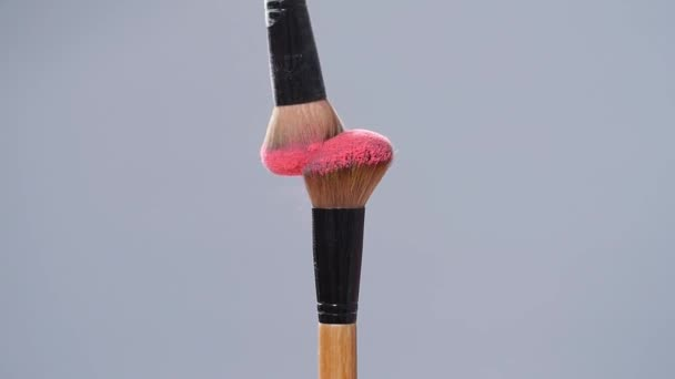 Make-up brush with pink powder splashes explosion on gray background on slow motion