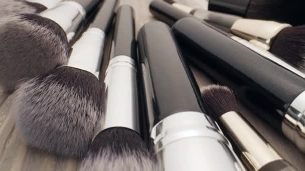 Cosmetics and beauty concept. Make-up brushes on wooden table