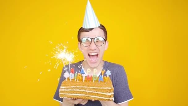 Všechno nejlepší k narozeninám. Mladý zábavný muž s dortem o oranžovém pozadí