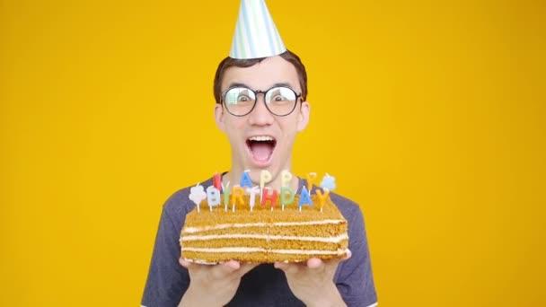Boldog születésnapot koncepció. Fiatal vicces ember süteménnyel o egy narancs háttér