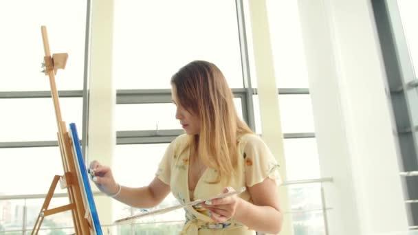 Artista femminile che lavora nel suo laboratorio, creando un quadro bellissimo, la pittura con oli colorati. Pittore donna disegno su tela