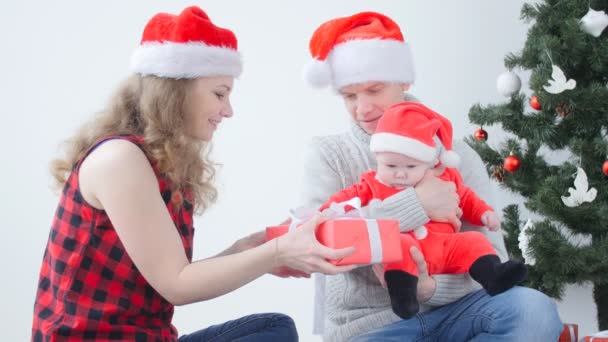 Family holiday and christmas concept. Young mother and father with a child unpack a Christmas present