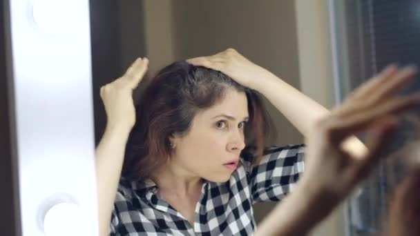 Young Frustrated woman looks in the mirror and plucks a grey hair from her head. Concept photo of young woman getting old