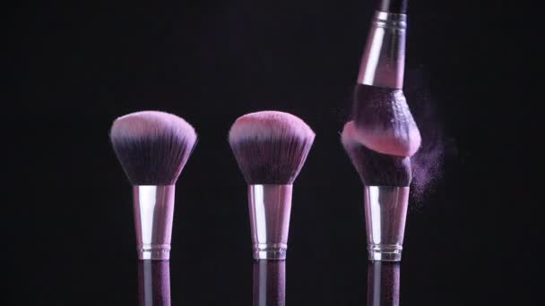 Beauty concept. Cosmetic brushes with pink cosmetic powder spreading on black background in slow motion
