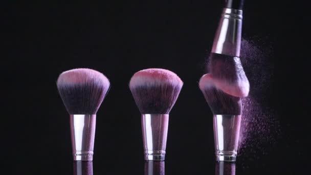 Szépség koncepció. Kozmetikai kefék rózsaszín kozmetikai porral fekete alapon lassított felvételben