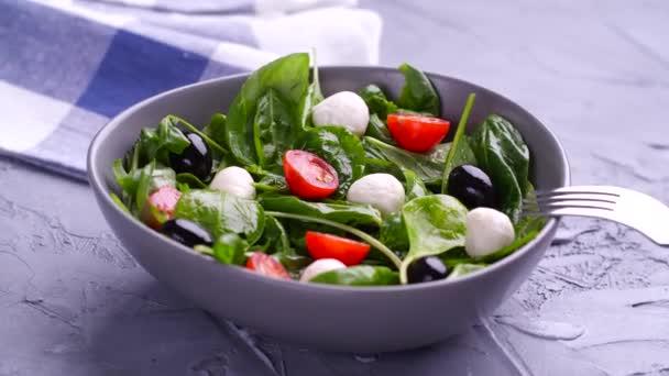 Vegetariánská a ekologická výživa. Salát Caprese italský nebo středomořský. Rajčatová mozzarella bazalka listy černé olivy a olivový olej otáčet