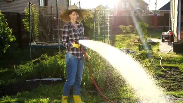 Young woman watering plants in her garden with garden hose. Hobby concept