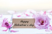 Writing happy valentine on card with rose on notebook.