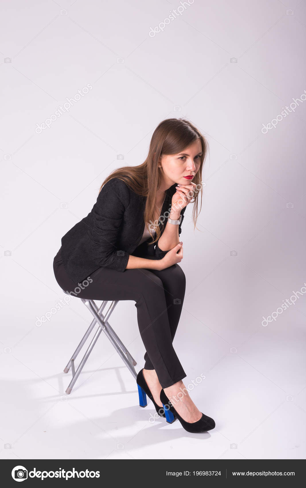 黒のスーツ、ハイヒールの靴、白い背景の上の椅子に座っている若いビジネス ・ ウーマンの完全な長さのスタジオ ポートレート \u2014 [著者]の写真  Satura_